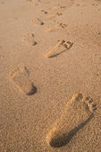 Print Foot symbol on sand texture background. — Stock Photo