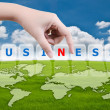 Hand putting Business word on the blue sky field. - Stock Photo