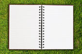 White notebook on grass field texture. — Stock Photo