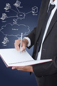 Businessman write on notebook with LAN diagram on the whiteboard. — Stock Photo