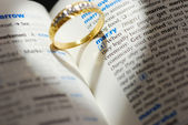 Wedding ring casting a heart onto a marry word — Stock Photo