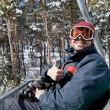 Man skier on chairlift in forest — Stock Photo