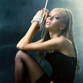 A beautiful woman with a rope knitted in the smoke — Stock Photo