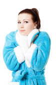 Young attractive woman in sky-blue bathrobe isolated on white — Stock Photo