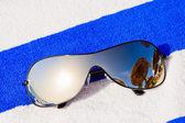 Mirrored sunglasses reflecting sun and sunshade — Stock Photo