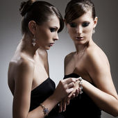 Two beautiful woman in black dress with jewelry — Stock Photo