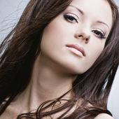 Bella mujer con una piel perfecta y pelo largo y negro exuberante — Foto de Stock