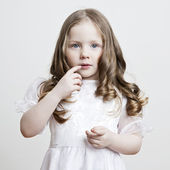 Portrait of a beautiful little girl in a white dress and veil on a white background — Stock Photo