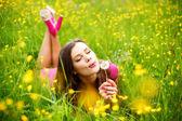 Woman blow on dandelion — Stock Photo