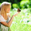 Woman playing with a butterfly — Stockfoto