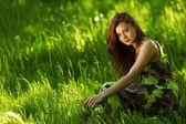 Brunett sitter på grönt gräs — Stockfoto
