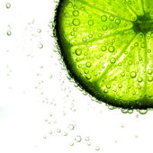 Lime slice in water — Stock Photo
