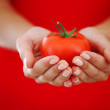 Tomato in woman hands — Stock Photo