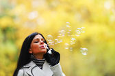 Autumn woman blow bubbles — Foto de Stock