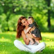 Mother and daughter on the green grass — Stock Photo #8515672
