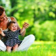 Mother and daughter on the green grass — Stock Photo #8515673