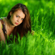 Stock Photo: Brunette lying on green grass