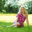 Blonde sitting on green grass — Stock Photo