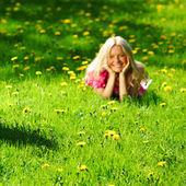 Girl on dandelion field — Stock Photo
