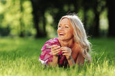 Blonde lying on green grass — Stock Photo