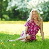 Blondin sitter på grönt gräs — Stockfoto