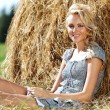 Stock Photo: Girl next to a stack of hay