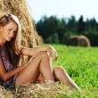Girl next to a stack of hay — Stock Photo #8528367
