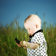 Stock Photo: Boy in grass call by phone