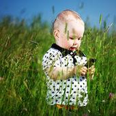 Boy in grass call by phone — Stok fotoğraf