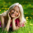 Girl on dandelion field — Stockfoto