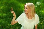 女人玩着一只蝴蝶 — 图库照片