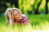 блондинка, лежа на зеленой траве — Стоковое фото