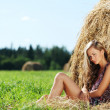 Royalty-Free Stock Photo: Girl next to a stack of hay