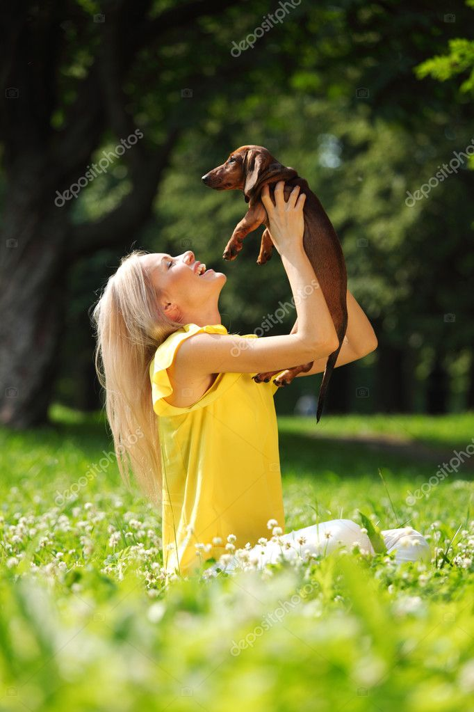 Woman dachshund in her arms on grass — Stock Photo #9030652