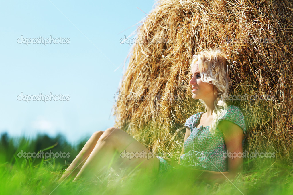 Portrait of a girl next to a stack of hay under the blue sky — Stock Photo #9030765