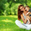 Mother and daughter on the green grass — Stock Photo #9147923