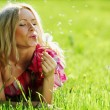 Girl blowing on a dandelion - Foto Stock