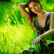 Brunette sitting on green grass — Stock Photo
