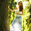 Girl standing next to a tree - Stock Photo