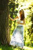 Girl standing next to a tree — Stock Photo