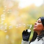Autumn woman blow bubbles — Stock Photo #9495390