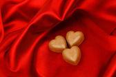 конфеты сердца на красная атласная — Стоковое фото
