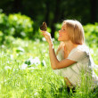 Woman playing with a butterfly - Stock Photo