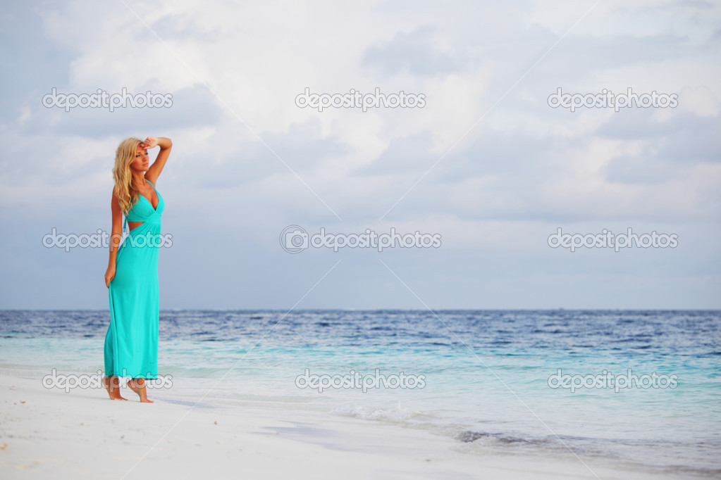 Woman in a blue dress on the ocean coast  Stock Photo #9974661