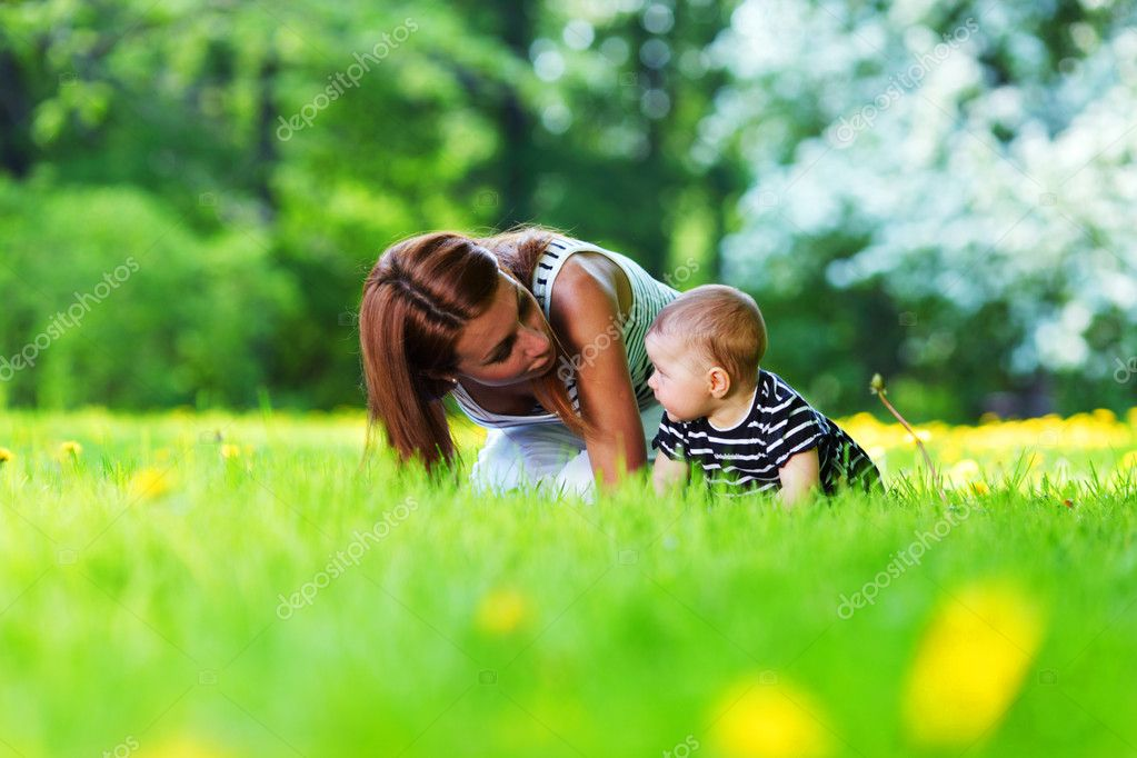 Happy mother and daughter on the green grass — Stock Photo #9975671