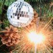 Christmas tree, mirror ball and lit sparkler. — Stock Photo