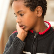 Portrait of an Ethiopian boy resting his chin on his hands — Stock Photo