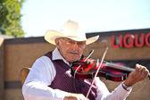 Old man playing a violin at a parade — Stock Photo