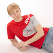 Young man in a red t-shirt lying on a white background — Stock Photo