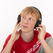 Young student boy dress in red hearing mp3 music, studio isolated on white — Stock Photo